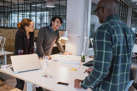회의에서 함께 서 성공적인 사업 동료. 사무실에서 테이블에 서있는 동안 다인종 창조적 인 팀이 작업을 논의. 스톡 콘텐츠