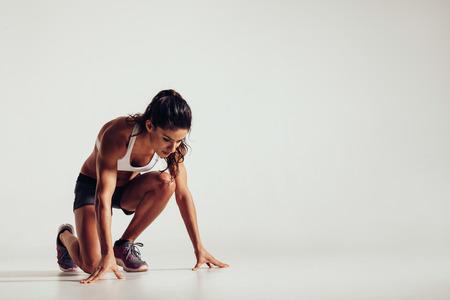 mujer deportista: Mujer joven sana que la preparación para una carrera. Fit atleta de sexo femenino listo para una primavera sobre fondo gris, con copia espacio. Foto de archivo