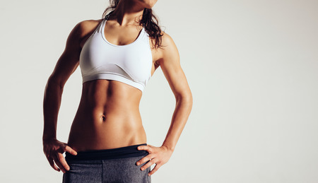 Close up of fit woman's torso with her hands on hips. Female with perfect abdomen muscles on grey background with copyspace. Stockfoto