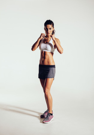 stance: Strong young woman doing boxing exercising in studio. Image of fit young female boxer against grey background.