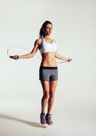 ropes: Healthy young woman skipping rope in studio. Muscular young woman exercising with jumping rope on grey background. Stock Photo