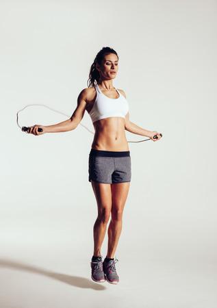 jump rope: Mujer joven sana que saltar la cuerda en el estudio. Mujer joven muscular que ejercita con saltar la cuerda en el fondo gris.