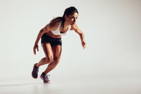 competencia: Mujer joven que empieza a ejecutarse y acelerando sobre fondo gris. Potente joven atleta femenina que se ejecutan en la competencia.