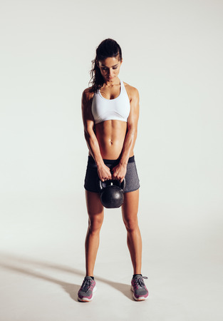 fitness woman: Pretty young woman exercising crossfit with kettle bell weight. Crossfit female working out on grey background. Focused female athlete doing body building exercise on grey background. Stock Photo