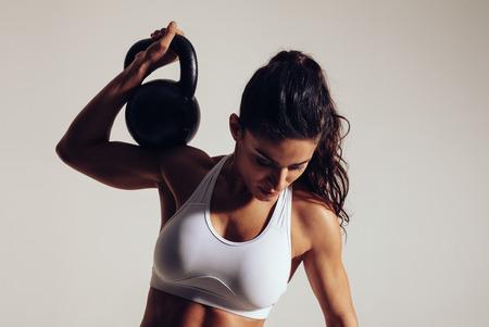 Bepaald jonge fitness vrouw uitoefenen met een waterkoker bell op grijze achtergrond. Vrouw in sportkleding doet CrossFit workout met één hand. Stockfoto