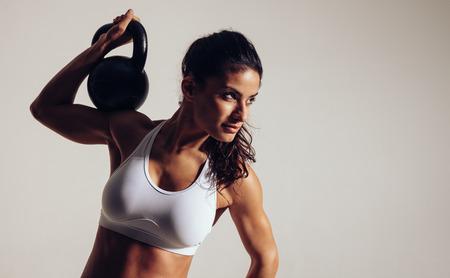 cuerpo femenino: Mujer joven centrada haciendo entrenamiento crossfit con campana hervidor de agua sobre fondo gris. Mujer en ropa de deportes que mira lejos el espacio de la copia, mientras que la sesi�n de entrenamiento crossfit.