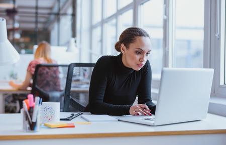 Beeld van de vrouw met behulp van laptop tijdens de vergadering op haar bureau. Jonge Afro-Amerikaanse zakenvrouw zitten in het kantoor en werk op laptop.