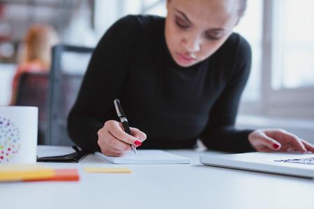 persona escribiendo: Mujer joven que trabaja en su escritorio tomando notas. Centrarse en mano escribiendo en un bloc de notas.