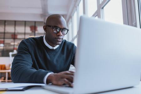 computadora: Hombre de negocios joven que trabaja en su computadora portátil en la oficina. Ejecutivo joven africano sentado en su escritorio navegar por internet en el ordenador portátil.