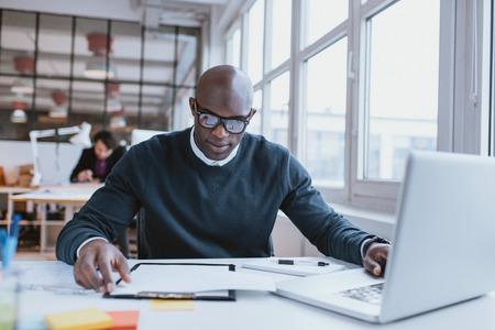 ejecutivo en oficina: Ejecutivo joven africano sentado en su escritorio con la computadora port�til que lee un documento. Hombre africano que trabaja en oficina.