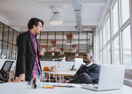 ejecutivo en oficina: Dos j�venes trabajadores de oficina con una reuni�n casual en el escritorio. La gente de negocios raza mixta que discuten el trabajo en oficina.