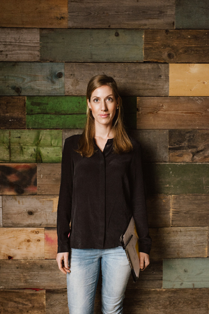 Portrait of beautiful young businesswoman standing against a wooden wall looking at camera. Caucasian woman in casuals in office. photo