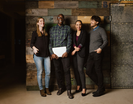 Portrait of young professionals laughing while standing together in office. Multi ethnic business team looking happy together. Reklamní fotografie
