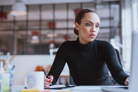 mujer trabajadora: Imagen de joven africano trabajando nueva misi�n empresarial. Ejecutivo de sexo femenino que se sienta en su escritorio con ordenador port�til y escribir notas en la oficina.