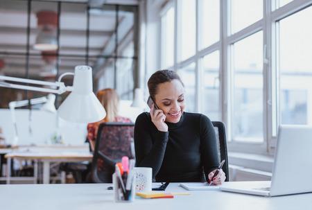 personas platicando: Mujer joven feliz que toma notas mientras habla por teléfono móvil. Mujer africana trabaja en su escritorio de contestar una llamada telefónica.