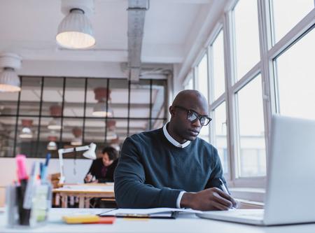 persona escribiendo: Hombre africano escribiendo notas mientras se trabaja en un ordenador port�til en una oficina moderna. Hombre joven ocupado trabajando en su escritorio.