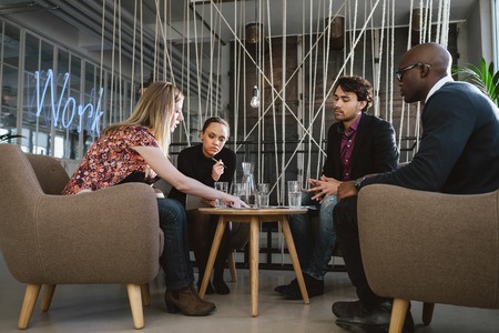 4 people: Diverse group of executives meeting in office sharing creative ideas. Young people having a meeting in lobby with woman showing something to coworkers. Stock Photo
