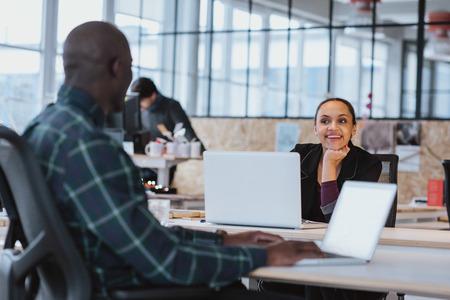 trabajo en la oficina: dise�adores creativos j�venes que tienen discusi�n amistosa en la oficina. mujer de raza negra sentado en la mesa de trabajo discutiendo con su colega.