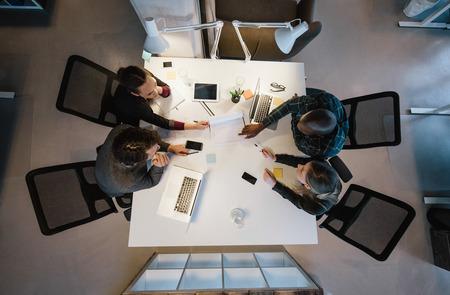 oficina: Los trabajadores de oficina se re�nen alrededor de una mesa para hacer la investigaci�n y poner en pr�ctica nuevas ideas. Vista de �ngulo alto de los hombres de negocios multi�tnicos discutiendo en la reuni�n de sala de juntas Foto de archivo