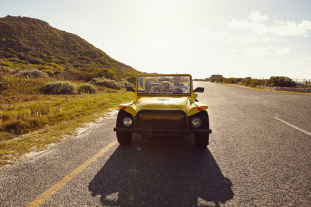Loving couple driving in a small open topped vehicle on a summer day. Young couple on road trip in beach buggy car. photo