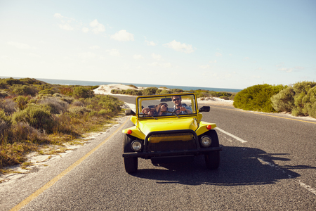 Happy couple in buggy car on open road. Friends driving on summer road trip.