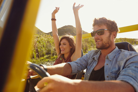 woman driving car: Happy couple enjoying on a long drive in a car. Friends going on road trip on summer day. Caucasian young man driving a car and joyful woman with her arms raised.