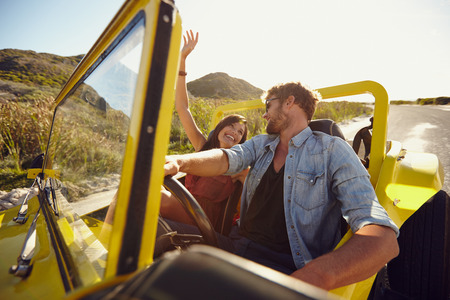 Beautiful young couple having fun on road trip. Man driving beach buggy on summer day with his girlfriend. photo