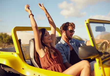 陽気な若いカップルが車を運転します。道路の旅を楽しんでいます。若い男と彼女の手を上げて乗車を楽しむ女性と車の運転。