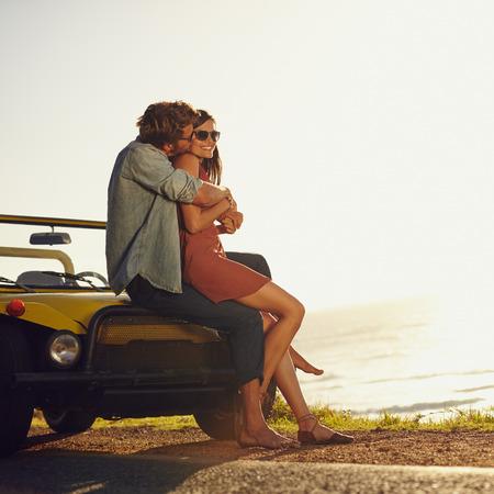 enamorados besandose: Joven pareja en abrazar el amor y besos. Hombre joven y mujer que se sienta en su capó del coche. Joven pareja romántica en viaje por carretera. Foto de archivo