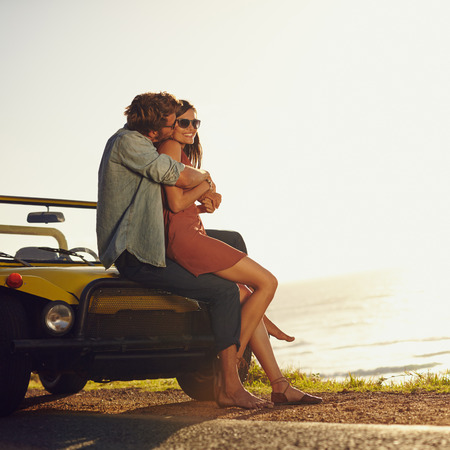 cars road: Young couple in love embracing and kissing. Young man and woman sitting on their car hood. Romantic young couple on road trip. Stock Photo