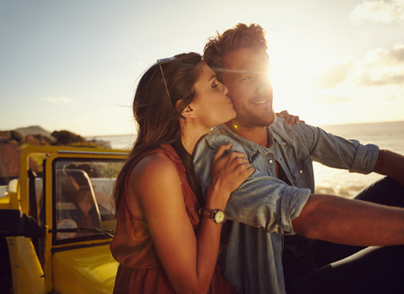 Romantic young couple sitting on the hood of their car while out on a roadtrip. Beautiful young woman kissing her boyfriend looking away smiling, outdoors.