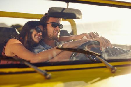 manejando: Retrato de la joven pareja romántica de ir en un largo viaje en coche abierto en un día de verano. Apuesto joven con su bella novia en un viaje por carretera. Foto de archivo