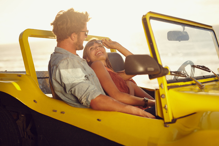 Romantic young couple in a car. Young woman looking at her boyfriend smiling. Couple on a road trip on a summer day. photo