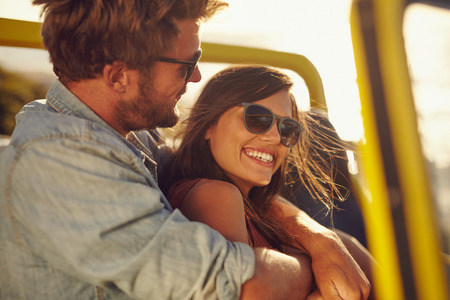 Portrait of loving young couple enjoying themselves on a road trip. Cheerful young man and woman in a car on holiday. photo