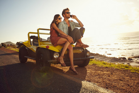 Portrait of young couple sitting on a their car by the sea shore, with man using mobile phone. Couple on holiday on a sunny summers day. photo