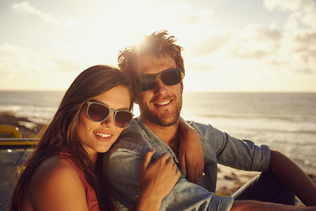 Portrait of beautiful young couple wearing sunglasses looking at camera while on a road trip. Young man and woman with beach in background. Archivio Fotografico