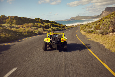 open topped: Rear view young couple driving in a small open topped vehicle. Love couple on road trip in beach buggy car.
