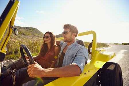 Beautiful young couple sitting in their car and enjoying the road trip. Man driving a car on an open road. Couple on summer holiday. Stock Photo