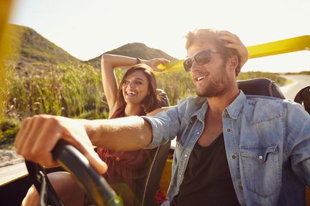 aandrijvingen: Vrolijk jong paar op road trip. Jonge man rijden geopend overgoten auto met vrouw lachend. Stockfoto