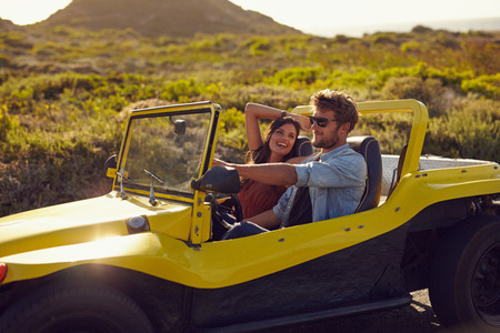 cars on the road: Portrait of happy young couple on a road trip in a beach buggy. Smiling young woman with her boyfriend driving car in countryside.