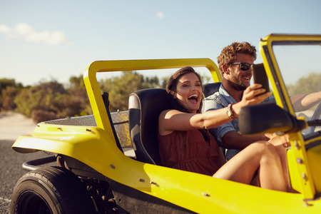 Excited happy couple enjoying road trip in their beach buggy. Man driving the car young woman taking a selfie from her mobile phone. Stock Photo