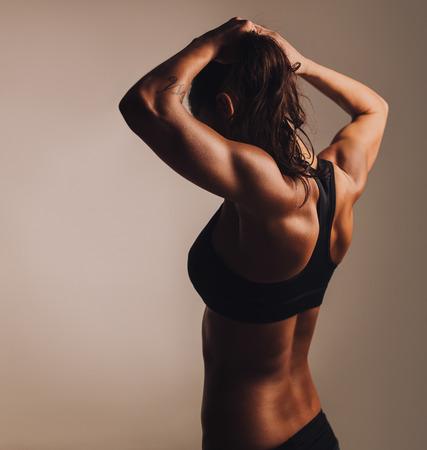 weiblich: Rückansicht der jungen Frau Bodybuilder zeigt muskulösen Körper. Fitness weiblichen zeigt muskulösen Rücken.