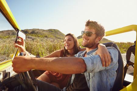 conduciendo: Hombre que conduce el coche con la mujer que toma selfie en su tel�fono inteligente. Pareja que se divierten en viaje por carretera en un d�a de verano. Foto de archivo