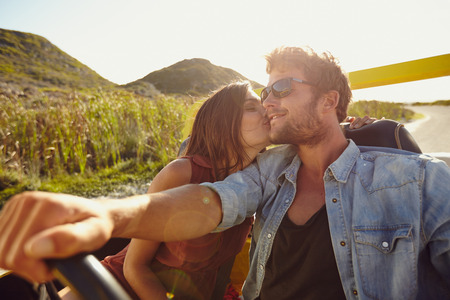 day trip: Woman kissing her boyfriend driving a car. Lovely young couple on road trip. Affectionate caucasian couple enjoying road trip. Stock Photo