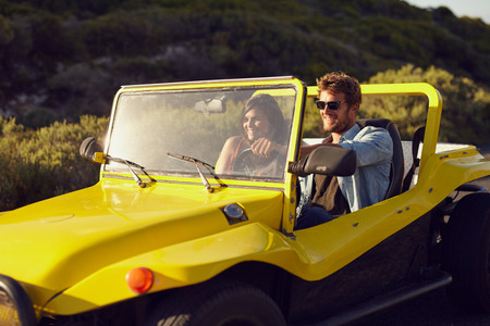 open topped: Shot of a handsome young man driving a car in the countryside with his girlfriend. Cheerful young couple on a road trip in a open topped vehicle. Stock Photo