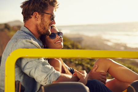 Portrait of beautiful young couple sitting together in a car smiling on a summer day. Romantic young couple enjoying the each others company outdoors photo