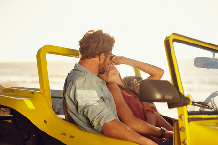 Affectionate young couple in a car. Young couple sharing a romantic moment while on a road trip. photo