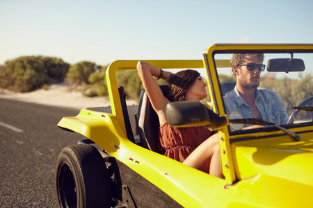 Romantic young couple on a road trip in a car. Caucasian young man and woman going on a holiday in buggy car. Woman with her boyfriend on long drive in countryside.