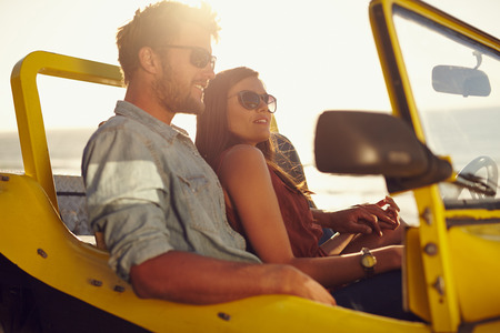 Portrait of beautiful young couple sitting together in a car. Romantic young couple enjoying the each others company on road trip. photo