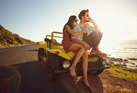 road of love: Relaxed young couple sitting on the hood of their car alongside a open coastal road with man answering a phone call and woman sitting by. Young couple on road trip.